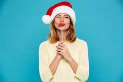 年轻可爱的妇女特写镜头圣诞老人握在棍子的` s帽子的纸嘴唇,当眨眼一只眼睛时 免版税库存照片