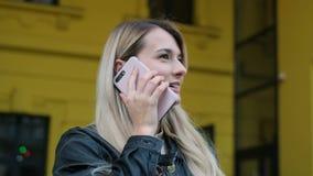年轻可爱的妇女画象一个断裂的,使用户外智能手机 有长发谈话的白肤金发的女孩在电话 股票录像