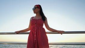 年轻可爱的妇女画象减速火箭的红色礼服和太阳镜的在日出或日落期间的海附近 美丽 股票视频