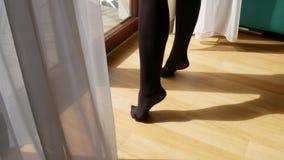 年轻可爱的妇女的特写镜头性感的腿 开放帷幕和站立在窗口附近在旅馆里 r 股票视频