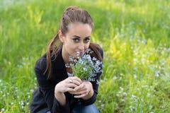 年轻可爱的妇女给她的面孔带来了勿忘草花束  图库摄影
