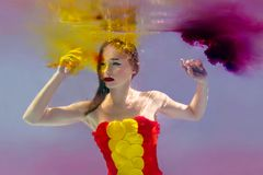 年轻可爱的妇女超现实的画象有气泡的水下在与墨水的五颜六色的水中 免版税库存图片