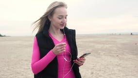 年轻可爱的妇女选择在电话的音乐训练的 移动播放表 影视素材