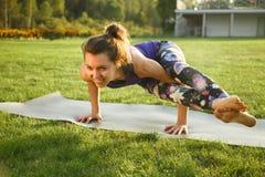 年轻可爱的室外女孩实践的瑜伽 在杉木常设夏天日落结构树二之后 免版税库存照片