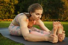 年轻可爱的室外女孩实践的瑜伽 在杉木常设夏天日落结构树二之后 图库摄影