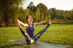 年轻可爱的室外女孩实践的瑜伽 在杉木常设夏天日落结构树二之后 库存照片