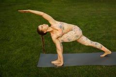 年轻可爱的室外女孩实践的瑜伽 在杉木常设夏天日落结构树二之后 免版税图库摄影