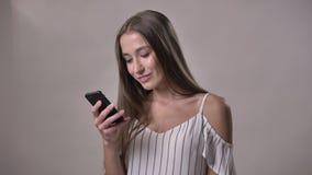 年轻可爱的害羞的女孩键入在智能手机的消息,观看在照相机,微笑,通信概念,灰色 股票视频