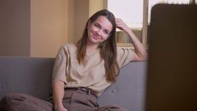 年轻可爱的微笑白种人女性的看着电视特写镜头画象愉快地坐长沙发户内在 影视素材