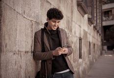 年轻可爱的愉快的行家人谈话在智能手机在欧洲城市 免版税图库摄影