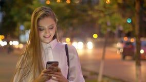 年轻可爱的感兴趣的女孩在晚上键入在她的智能手机的消息在夏天,微笑,通信 股票录像