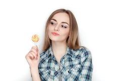 年轻可爱的新鲜的看起来的白肤金发的妇女秀丽画象摆在与糖果棒棒糖的蓝色格子花呢上衣的 情感和面部前 免版税库存照片
