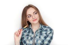 年轻可爱的新鲜的看起来的白肤金发的妇女秀丽画象摆在与糖果棒棒糖的蓝色格子花呢上衣的 情感和面部前 免版税图库摄影