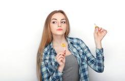 年轻可爱的新鲜的看起来的白肤金发的妇女秀丽画象摆在与糖果棒棒糖的蓝色格子花呢上衣的 情感和面部前 库存照片