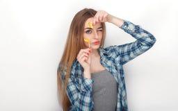 年轻可爱的新鲜的看起来的白肤金发的妇女秀丽画象摆在与糖果棒棒糖的蓝色格子花呢上衣的 情感和面部前 图库摄影