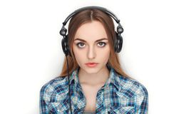 年轻可爱的新鲜的看起来的白肤金发的妇女秀丽画象摆在大dj耳机的蓝色格子花呢上衣的 情感和面部expr 免版税图库摄影