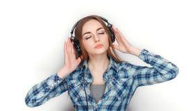 年轻可爱的新鲜的看起来的白肤金发的妇女秀丽画象摆在大dj耳机的蓝色格子花呢上衣的 情感和面部expr 库存照片