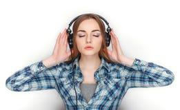 年轻可爱的新鲜的看起来的白肤金发的妇女秀丽画象摆在大dj耳机的蓝色格子花呢上衣的 情感和面部expr 库存图片