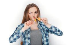 年轻可爱的新鲜的看起来的白肤金发的妇女秀丽画象摆在糖果棒棒糖的蓝色格子花呢上衣的 明确的情感和的脸面护理 免版税图库摄影