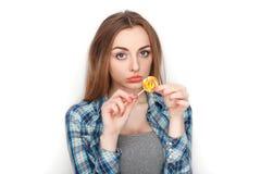 年轻可爱的新鲜的看起来的白肤金发的妇女秀丽画象摆在糖果棒棒糖的蓝色格子花呢上衣的 明确的情感和的脸面护理 免版税库存图片