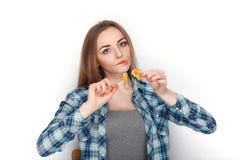年轻可爱的新鲜的看起来的白肤金发的妇女秀丽画象摆在糖果棒棒糖的蓝色格子花呢上衣的 明确的情感和的脸面护理 库存照片