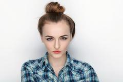 年轻可爱的新鲜的看起来的白肤金发的妇女秀丽画象有高小圆面包头发混乱的在蓝色格子花呢上衣 情感和面部expr 库存图片