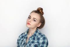 年轻可爱的新鲜的看起来的白肤金发的妇女秀丽画象有高小圆面包头发混乱的在蓝色格子花呢上衣 情感和面部expr 库存照片