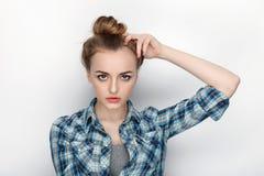 年轻可爱的新鲜的看起来的白肤金发的妇女秀丽画象有高小圆面包头发混乱的在蓝色格子花呢上衣 情感和面部expr 图库摄影