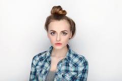年轻可爱的新鲜的看起来的白肤金发的妇女秀丽画象有高小圆面包头发混乱的在蓝色格子花呢上衣 情感和面部expr 免版税图库摄影
