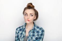 年轻可爱的新鲜的看起来的白肤金发的妇女秀丽画象有高小圆面包头发混乱的在蓝色格子花呢上衣 情感和面部expr 免版税库存图片