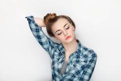 年轻可爱的新鲜的看起来的白肤金发的妇女秀丽画象有高小圆面包头发混乱的在蓝色格子花呢上衣 情感和面部expr 免版税库存照片