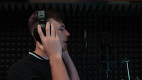 年轻可爱的男孩情感地唱歌 帅哥在专业录音室微笑着 股票视频