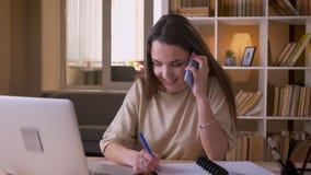 年轻可爱的白种人女实业家特写镜头画象有电话使用膝上型计算机户内在办公室 股票录像