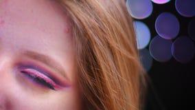 年轻可爱的白种人女性特写镜头半面孔射击有看照相机的桃红色美好的桃红色闪烁构成的 股票视频