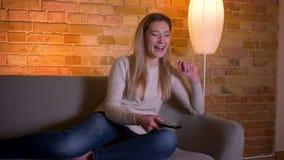 年轻可爱的白种人深色的女性看着电视和笑的选址特写镜头画象在长沙发户内在a 影视素材