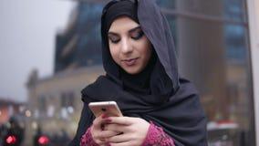 年轻可爱的站立在街道的妇女佩带的hijab特写镜头视图,键入在她的手机的一则消息