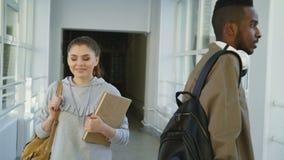 年轻可爱的美丽的女孩沿着走梦想通过宽宽敞大学的走廊查寻和  股票录像
