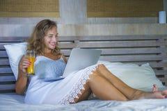 年轻可爱的美丽的愉快的妇女30s在床上在家使用运作在计算机膝上型计算机微笑的放松的饮用的orang的互联网 免版税图库摄影