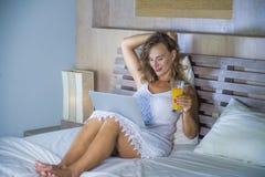 年轻可爱的美丽的愉快的妇女30s在床上在家使用运作在计算机膝上型计算机微笑的放松的饮用的orang的互联网 库存照片