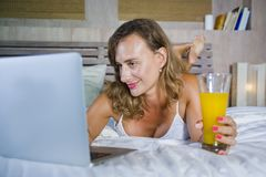 年轻可爱的美丽的愉快的妇女30s在床上在家使用运作在计算机膝上型计算机微笑的放松的饮用的orang的互联网 库存图片