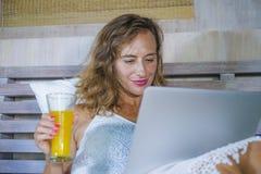 年轻可爱的美丽的愉快的妇女30s在床上在家使用运作在计算机膝上型计算机微笑的放松的饮用的orang的互联网 免版税库存图片