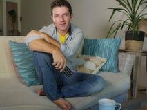 年轻可爱的英俊和愉快的人享受坐的放松的在家观看的电视电影或展示在客厅沙发cou 免版税库存图片