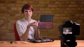 年轻可爱的行家女性录影博客作者放出活和给化妆用品做广告特写镜头射击,当谈话时 图库摄影