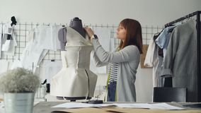 年轻可爱的裁缝测量裁缝与磁带的` s钝汉做与这些测量的新的服装 繁忙的日 影视素材