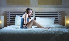 年轻可爱的西班牙妇女坐床遭受的胃痉挛疼痛和期间使感到痛苦病和不适在周期和p 图库摄影