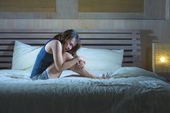 年轻可爱的西班牙妇女坐床遭受的胃痉挛疼痛和期间使感到痛苦病和不适在周期和p 免版税库存照片