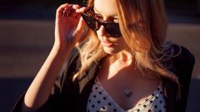 年轻可爱的金发碧眼的女人在热的夏天晚上改正太阳镜,在城市背景的画象 免版税库存图片