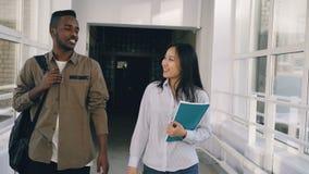 年轻可爱的非洲活泼谈论男性和亚裔的女学生移动在走廊下某事和 股票视频
