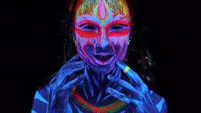 年轻可爱的bodyarted女孩接近的画象紫外光的在黑背景 黑轻的发光的油漆 股票视频
