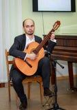 年轻吉他弹奏者坐与一把吉他的阶段在他的手上 免版税库存照片